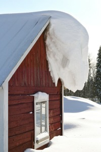 red barn with snow and ice hanging off of roof