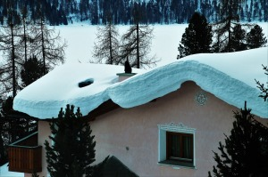 stucco house in the woods covered in thick snow
