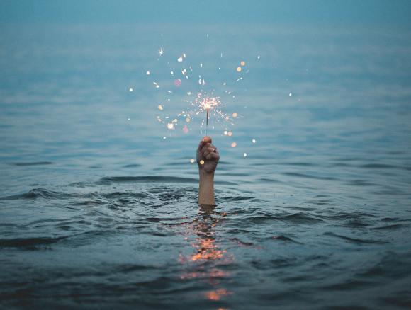 underwater hand holding a sparkler